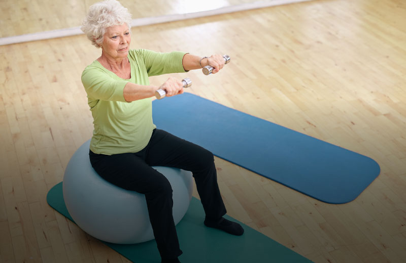 Elderly woman sitting on a fitness ball with weights